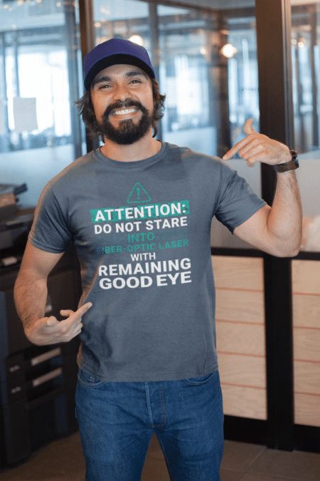 "Man smiling and pointing to a t-shirt that says ""Attention: do not stare into fiber-optic laser with remaining good eye"""