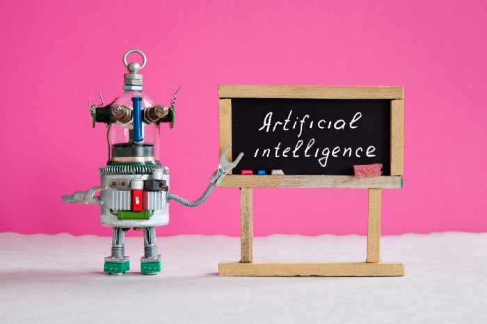 """Photo of a toy robot pointing to a sign that says """"Artificial Intelligence"""""""