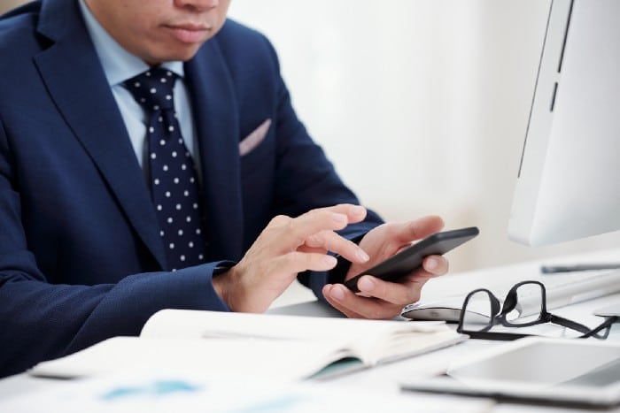 Photo of a man in a blue suit using a smartphone